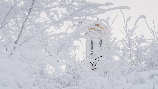 Beautiful orthodox white temple among snowy trees
