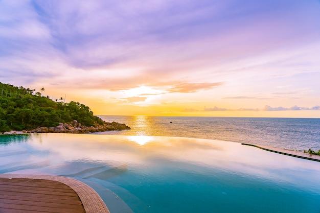 바다 바다 전망과 흰 구름 푸른 하늘이있는 호텔 리조트의 아름다운 야외 무한대 수영장