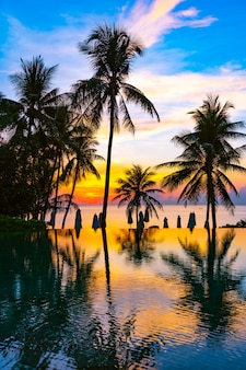 Beautiful outdoor nature landscape with sea ocean and coconut palm tree around swimming pool at sunrsie or sunset