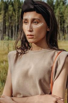 フェイスペイントと混血の若い女性の美しい屋外の肖像画