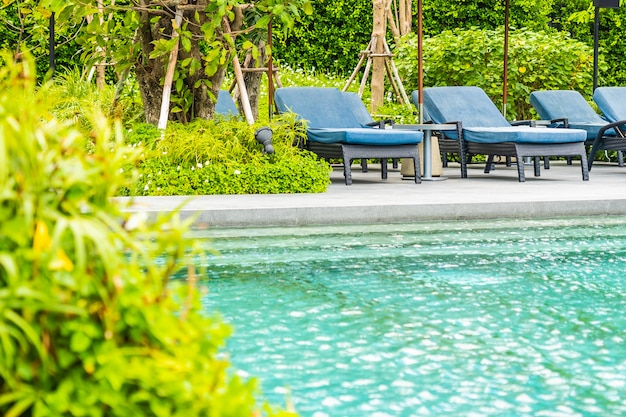 Beautiful outdoor swimming pool in hotel and resort with chair and deck for leisure vacation