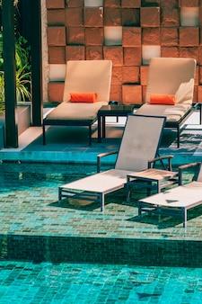 Красивый открытый бассейн в отеле и курорте с креслом и террасой для отдыха