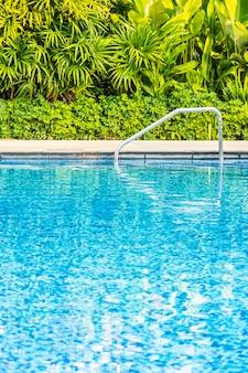 여행 및 휴가 리조트에서 침대 데크 의자와 우산이있는 아름다운 야외 수영장