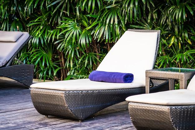旅行や休暇のためのリゾートのベッドデッキチェアと傘の美しい屋外スイミングプール