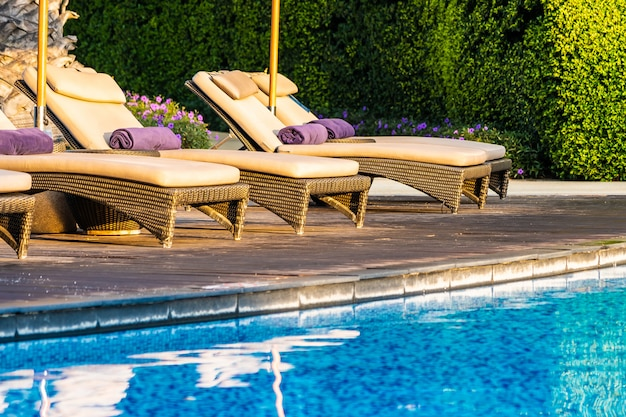 Beautiful outdoor swimming pool with bed deck chair and umbrella in resort for travel and vacation