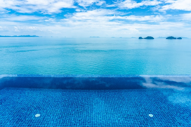 Beautiful outdoor swimming pool with sea ocean on white cloud blue sky