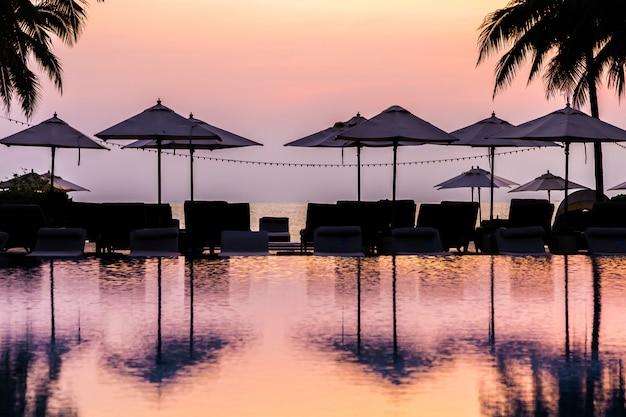 日の出時にリゾートで周りのシルエットの傘の椅子と美しい屋外スイミングプール