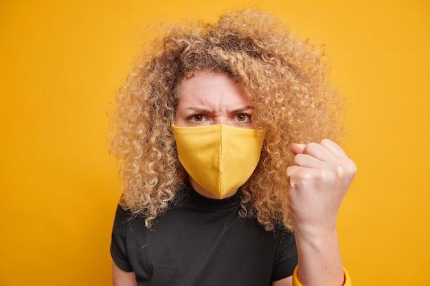 곱슬 머리 clenches 주먹을 가진 아름 다운 분노 젊은 여자는 노란색 벽 위에 고립 된 코로나 바이러스 전염병 동안 부정적인 감정을 표현하는 부정적인 감정을 표현한다