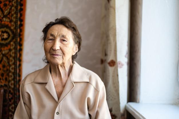 Красивая очень старая женщина дома у окна