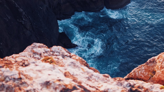Beautiful overhead shot of body of water with amazing textures hitting the cliffs in the sea