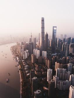 背の高い高層ビルと横に川がある上海の街のスカイラインの美しいオーバーヘッドショット