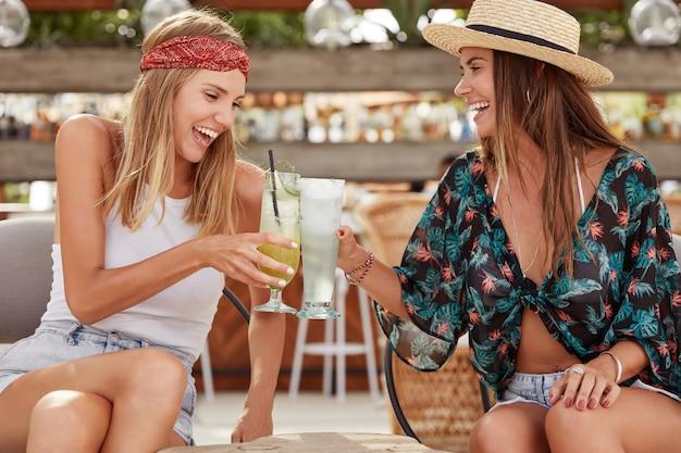 아름답고 기뻐하는 젊은 여성들은 함께 여름 파티를하고, 칵테일 한 잔을 마시 며, 좋은 레크리에이션을 즐기고, 즐거운 대화를 나눕니다. 쾌활한 가장 친한 친구는 여름 음료를 마신다. 휴식 시간