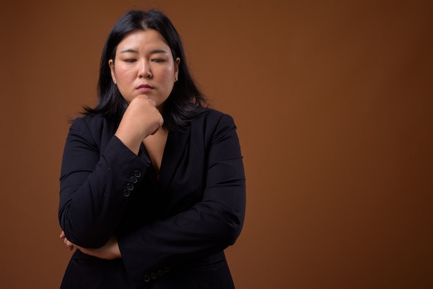 Beautiful overweight asian businesswoman on brown