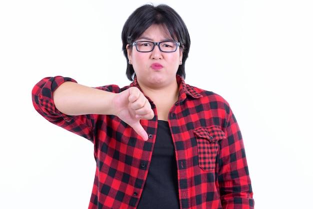 Красивая толстая азиатская хипстерская женщина с короткими волосами в очках изолирована у белой стены