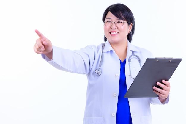 白い壁に対して隔離された眼鏡をかけている短い髪の美しい太りすぎのアジアの女性医師