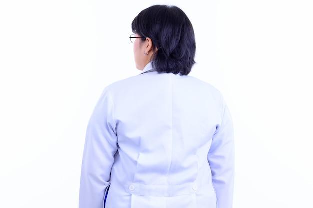 흰 벽에 고립 된 안경을 쓰고 짧은 머리를 가진 아름다운 과체중 아시아 여자 의사