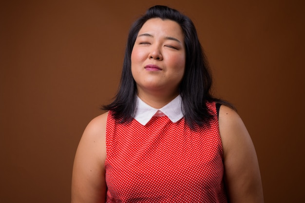 Красивая толстая азиатская женщина в красном платье