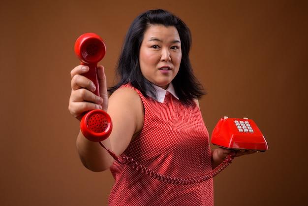 赤いドレスを着て美しい太りすぎのアジア女性