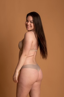 ピンクの背景にベージュの水着で美しい太りすぎの女性。高品質の写真
