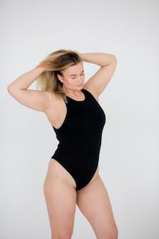 灰色の背景に黒い水着の美しい太りすぎの女性