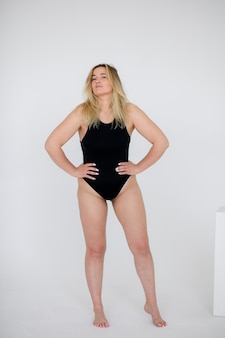 白い壁に黒い水着で美しい太りすぎの女性