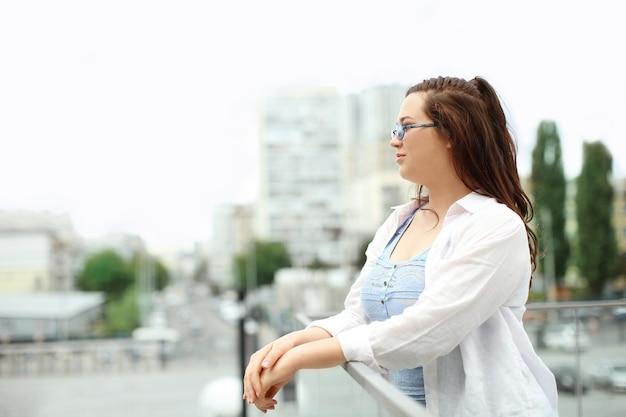 도시에서 옥상에 서있는 아름 다운과 체중 여자