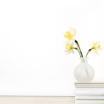 白い背景の前のテーブルの植木鉢に美しい淡い黄色の水仙の花。フラワーアレンジメント