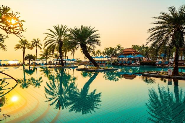 日の出時に高級ホテルリゾートの傘の椅子のプールと美しいヤシの木-休日と休暇のコンセプト