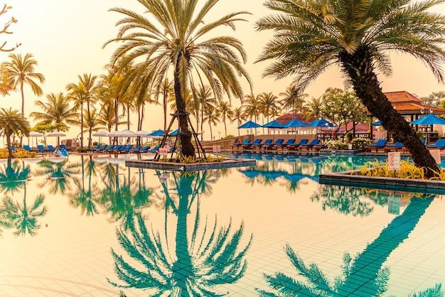 Красивая пальма с бассейном с зонтиком в роскошном курортном отеле во время восхода солнца. концепция праздника и отпуска