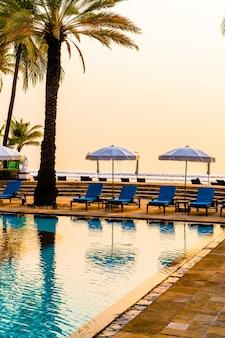 Красивая пальма с бассейном с зонтиком в роскошном курортном отеле во время восхода солнца - концепция отпуска и отпуска