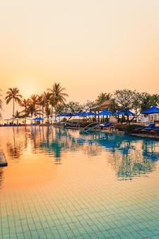 휴가 및 휴가 개념-일출 시간에 고급 호텔 리조트에서 우산 의자 수영장과 아름다운 야자수