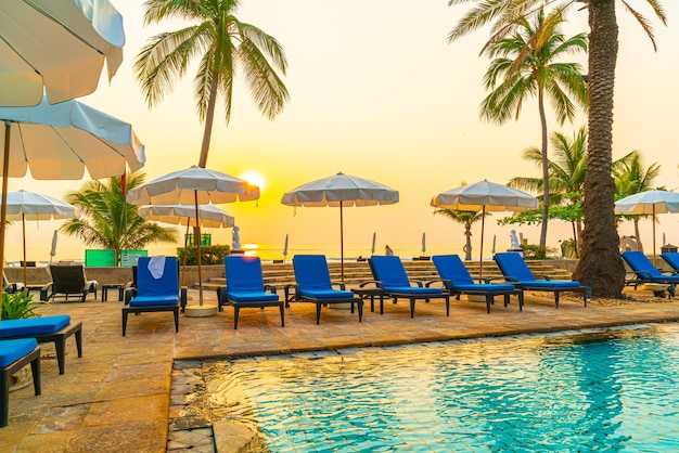 Красивая пальма с бассейном с зонтиком в роскошном курортном отеле