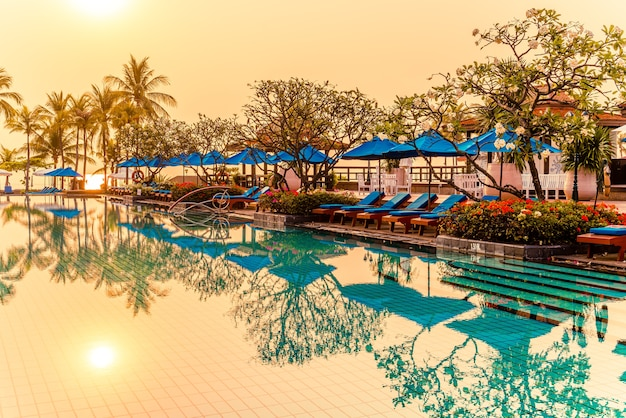 Beautiful palm tree with umbrella chair pool in luxury hotel resort at sunrise times. holiday and vacation concept