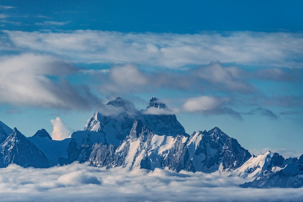 Beautiful panorama of high rocky mountains ushba with mighty glaciers against the blue sky and clouds