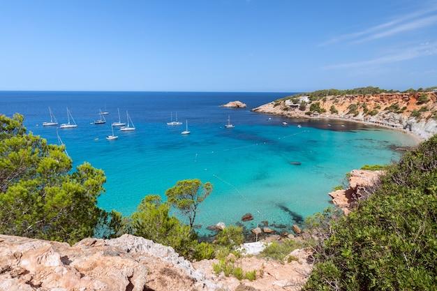 Красивая панорама бухты кала хорт с морских парусных яхт на ибице, испания