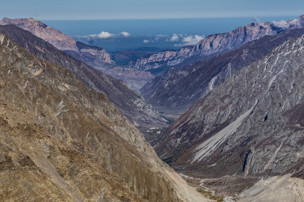 Красивая панорама высоких скалистых гор на фоне голубого неба и облаков