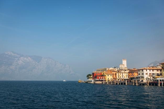 Красивая панорама озера гарда италия. вид на красивое озеро гарда с лодки в окружении гор