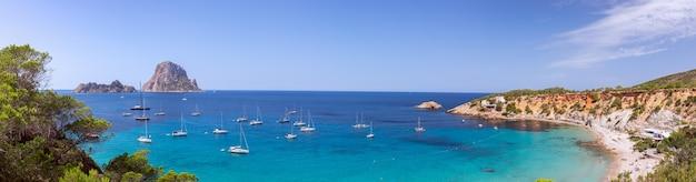 Прекрасная панорама пляжа кала хорт и горы эс ведра с морских парусных яхт. ибица, балеарские острова. испания