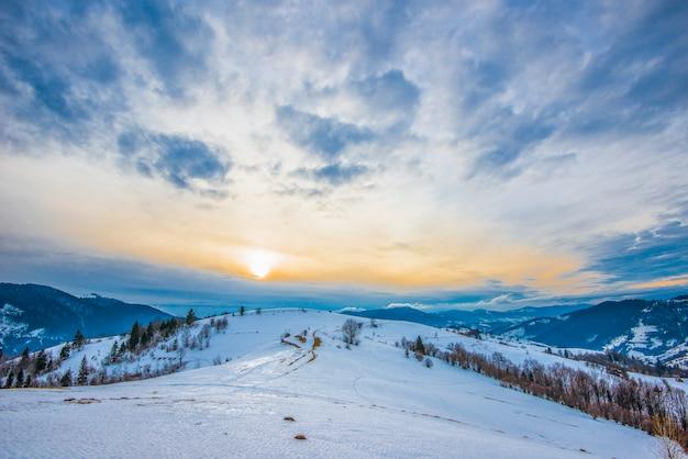 雪に覆われた山脈の美しいパノラマは、曇り空と夕日を見下ろすハイキングコースに分かれています。