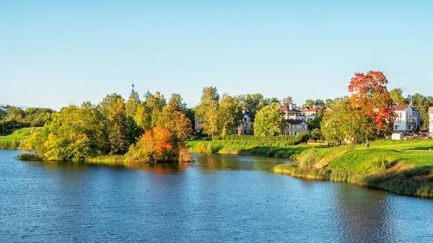 湖のほとりに明るい木々と美しいパノラマの秋の風景。