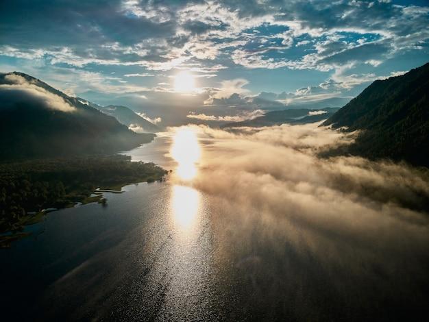 중간에 태양이 떠오르는 구름과 산 위의 아름다운 탁 트인 풍경.