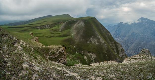 雨の高原の美しいパノラマ風景。緑の織り目加工の山々を背景に遠くまで伸びる岩だらけの棚。