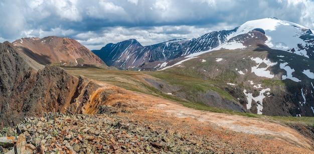 Красивый панорамный горный пейзаж с красными снежными скалами. большой скальный массив, различные скальные образования и слои почвы. далекое горное плато.