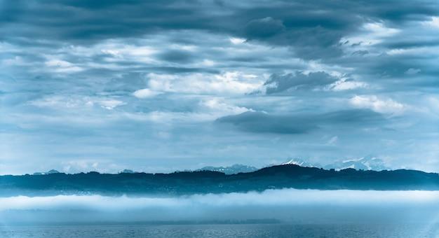 曇り空の下で背景に丘のある海の美しいパノラマ写真