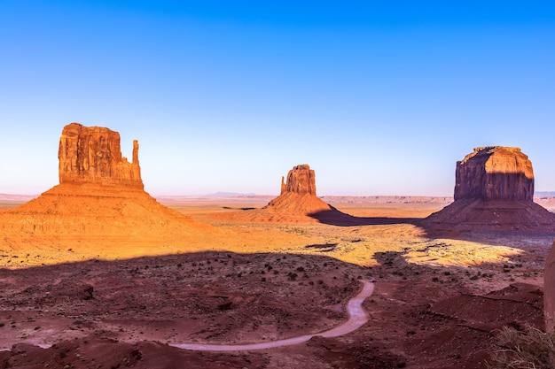米国アリゾナ州とユタ州の国境にあるモニュメントバレーの有名なビュートの美しいパノラマの夕日の景色 Premium写真
