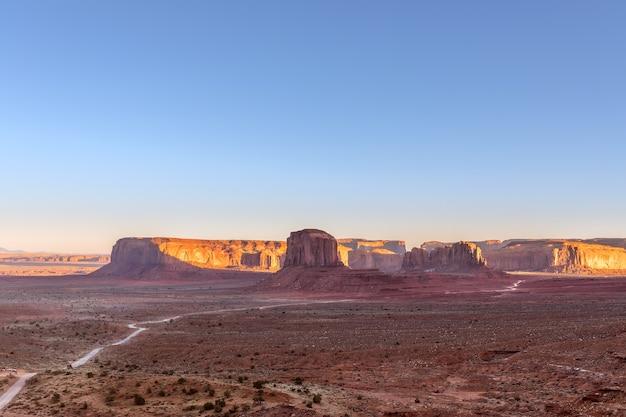 米国アリゾナ州とユタ州の国境にあるモニュメントバレーの有名なビュートの美しいパノラマの夕日の景色