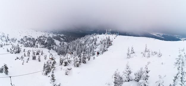 흐린 겨울 날에 케이블카가있는 스키베이스의 높은 지점에서 아름다운 전경