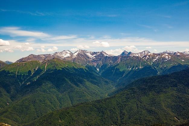 Прекрасный панорамный вид на высокие заснеженные горы в ясный солнечный день.