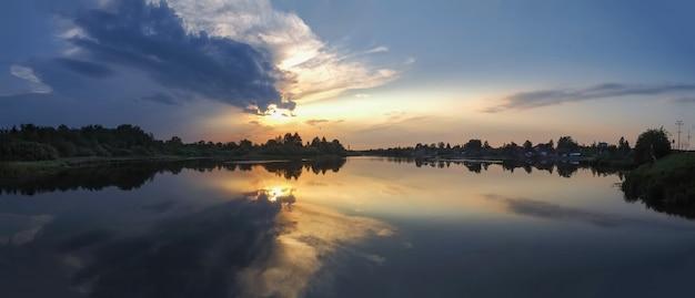 湖に沈む夕日と水の反射の美しいパノラマビュー。