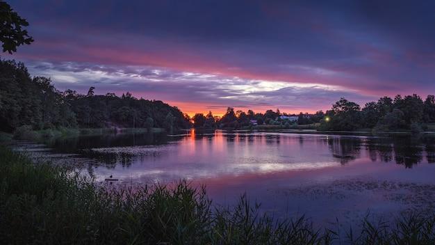 湖の紫の夕日の美しいパノラマの景色。